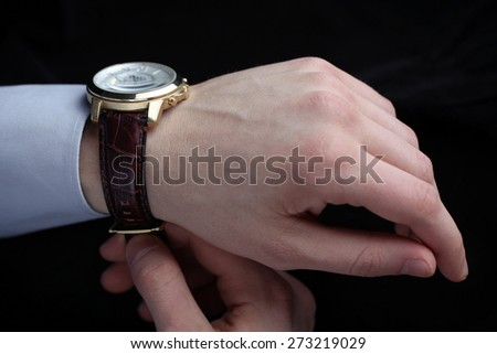 Man putting on wrist watch. Isoalted on black background, shallow focus. - stock photo
