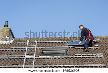 man putting the solar panel to the metal construction on the roof - stock photo