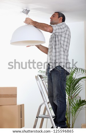 Man putting up a ceiling light - stock photo