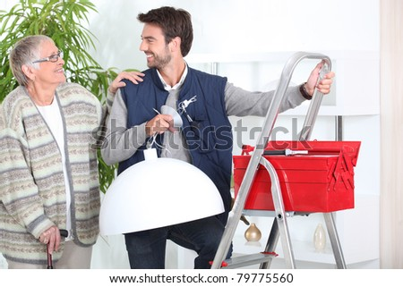 Man putting up a light for a senior - stock photo