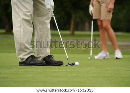 Man putting, woman in background, shallow dof. - stock photo