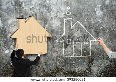 Man putting wooden house into hole of old mottled concrete wall, beside with woman hand drawing house doodles. - stock photo