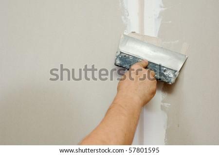 man putty plasterboard indoor - stock photo