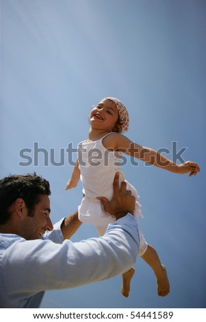 Man raising a little girl in his arms