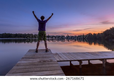 Man raising his arms while enjoying the sunset as a concept for a happy achievement - stock photo