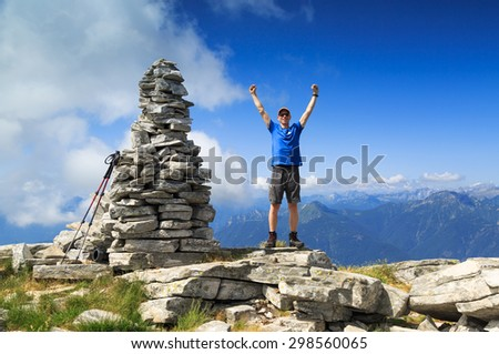 Man raising his hands out of joy for reaching the top of a mountain. - stock photo