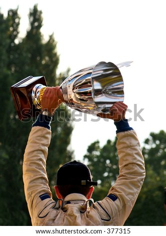 Man raising the winning trophy above his head. - stock photo