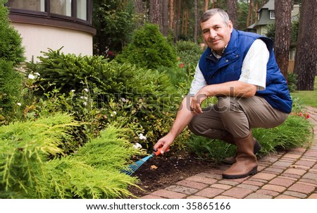 Man raking garden - stock photo