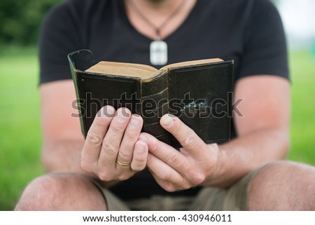 Man reading a bible outside