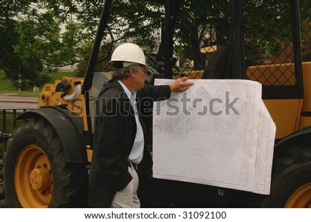 man reading a blueprint on a piece of construction equipment - stock photo