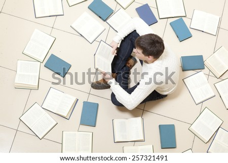 Man reading a book, top view. Blurred text is unreadable - stock photo
