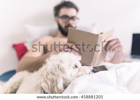Man reading a book while his dog lays beside him on his bed - stock photo
