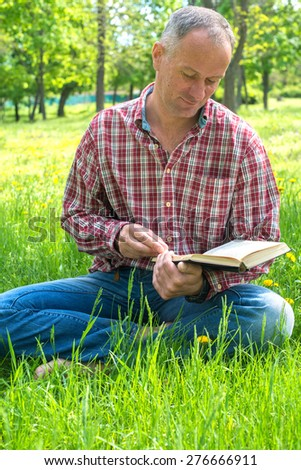 Man reading a book while sitting on a glade in park - stock photo