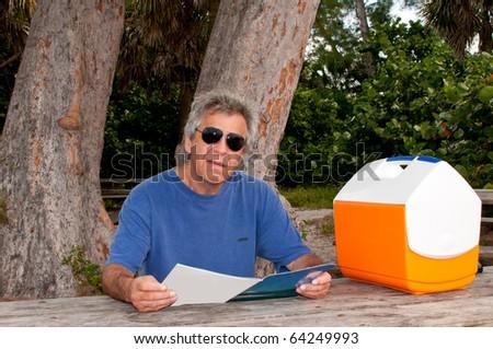 Man reading a magazine at a picnic table - stock photo