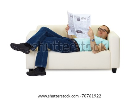 man reading a newspaper lying on the couch at home - stock photo