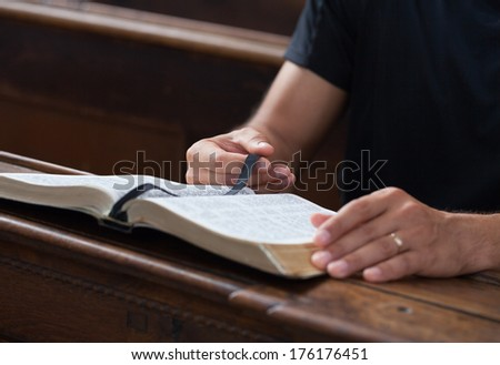 Man reading Bible in a church. - stock photo