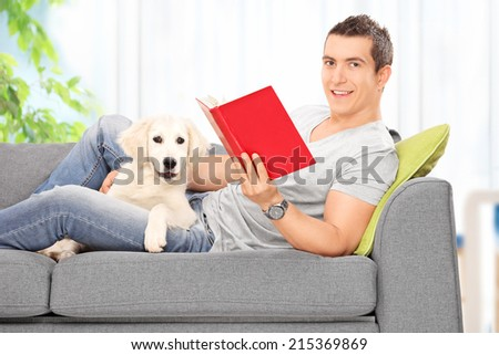 Man reading book and lying on sofa with a dog at home - stock photo