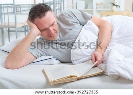 Man reading book in bed - stock photo