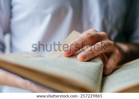 Man reading. Book in his hands. - stock photo