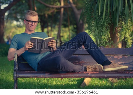 Man reading book outdoors in park