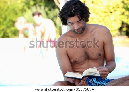 Man reading by the pool - stock photo