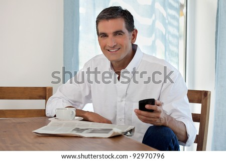Man Reading Morning Newspaper and Checking Phone - stock photo