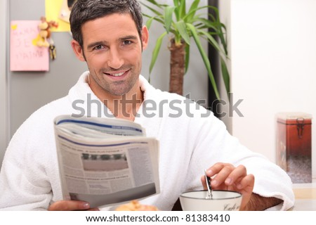 man reading newspaper and having breakfast - stock photo