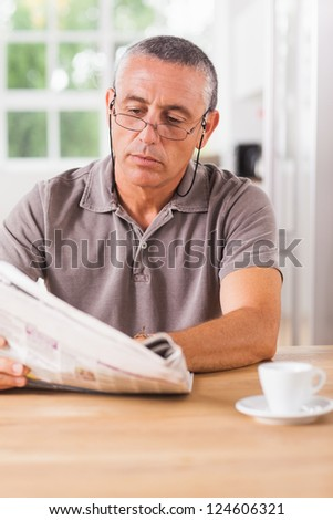 Man reading newspaper at kitchen table - stock photo