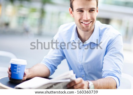 Man reading newspaper at outdoor cafe - stock photo