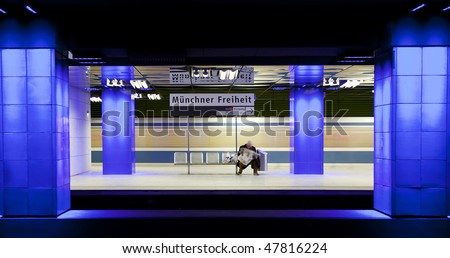 Man reading newspaper in munich underground, sitting on a bench between blue pillars and a train passing by in the back at high speed - stock photo