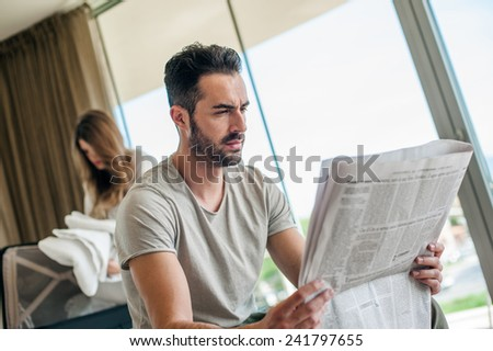 Man Reading Newspaper on Vacation - stock photo