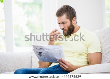 Man reading newspaper while having a coffee in living room