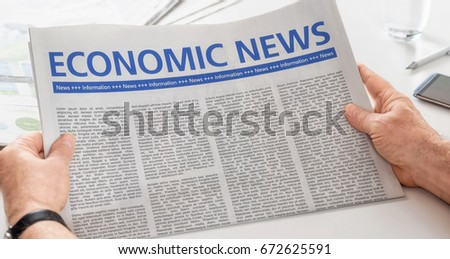 Man reading newspaper with the headline Economic News