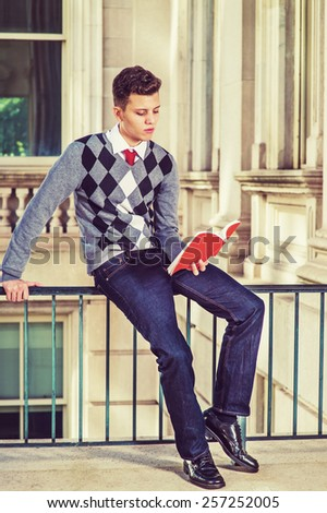 Man Reading Outside.  Dressing in black, white, gray patterned sweater, jeans, leather shoes, a young college student sitting on a railing in office building, reading a red book. Retro filtered look. - stock photo