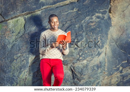 Man Reading Outside. Dressing in cream, patterned, collarless sweater, red jeans, wearing wristwatch, holding a red book, a young black guy is leaning against rocks, smiling, looking down, reading. - stock photo