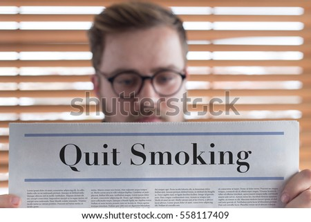 Man reading Quit Smoking headlined newspaper