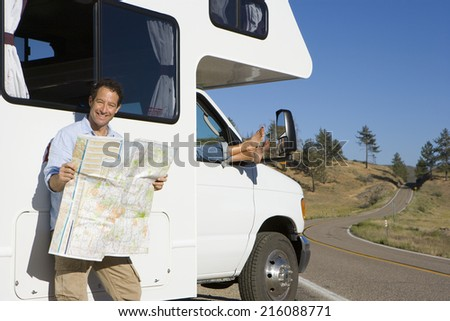 Man reading road map by woman with feet out of window of motor home - stock photo