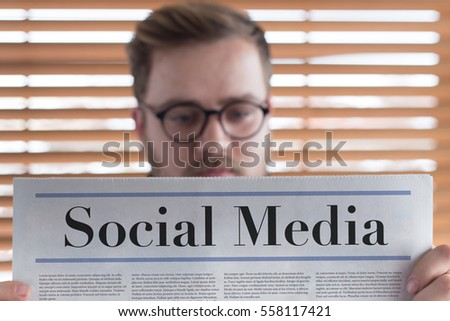 Man reading Social Media headlined newspaper