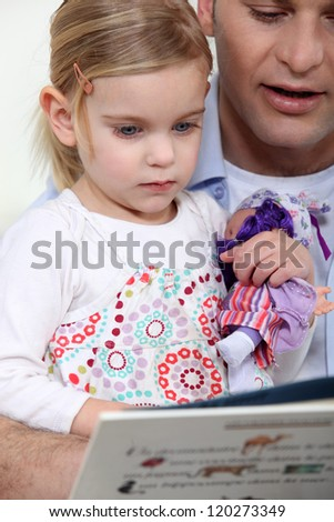 Man reading to his daughter - stock photo
