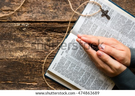 man reads a prayer from the Bible on the wooden background with space for text
