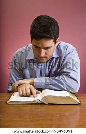 Man reads the Bible - stock photo