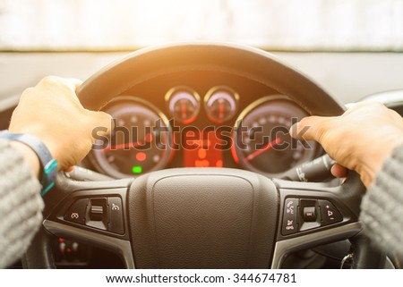 Man ready for driving the car on the freeway. Close up of hands of driver on steering wheel of car. Personal point of view of machine's front glass. Main focus on the lather. - stock photo