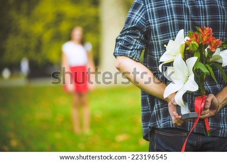 Man ready to give flowers to girlfriend - stock photo