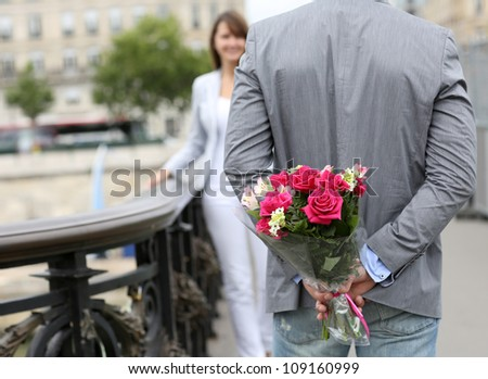 Man ready to give flowers to girlfriend on a bridge