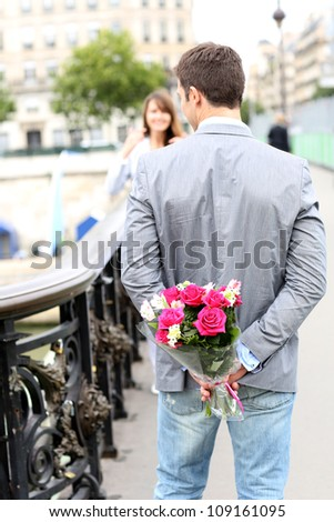 Man ready to give flowers to girlfriend on a bridge - stock photo