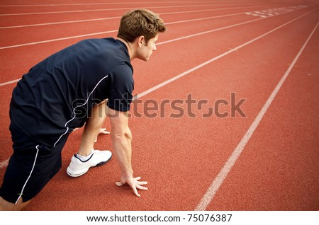 Man ready to start running on a track - stock photo