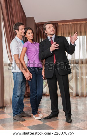 man real estate agent showing hugging couple new house. male agent showing view from new house window - stock photo