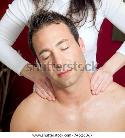 Man receiving a shoulder massage by therapist - stock photo