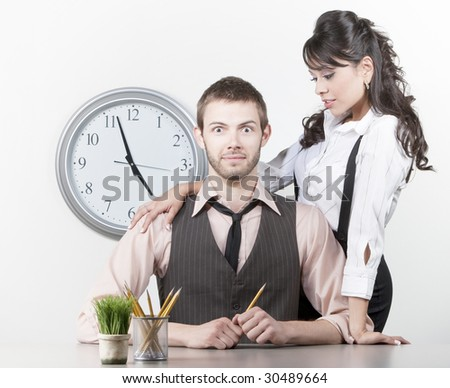 Man receiving attention from a pretty Hispanic coworker - stock photo