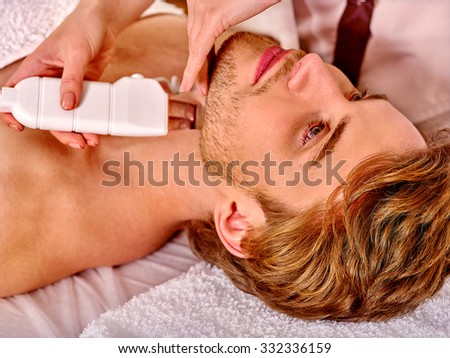 Man receiving electric facial peeling at beauty salon.  - stock photo